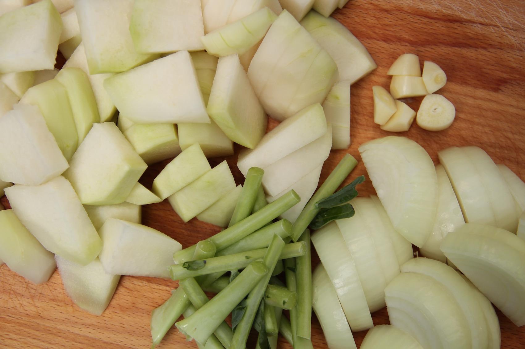 Kohlrabi, Zwiebeln, Knoblauch und Kohlrabiblätterstiele klein geschnitten