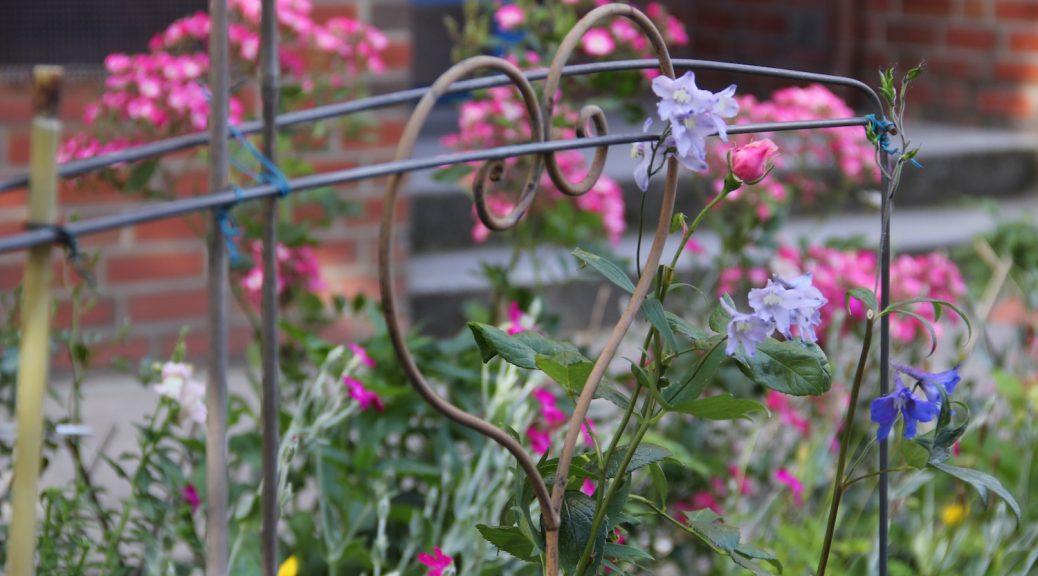 ein Drahtherz im Blumenbeet
