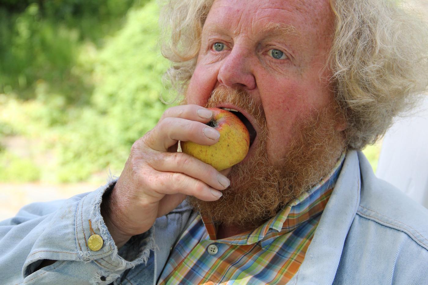Eckart Brandt beißt in einen Apfel.
