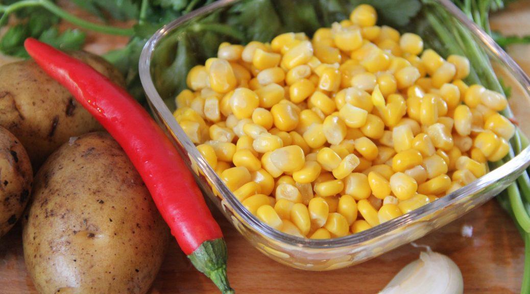 Frische Zutaten für eine Maissuppe: Mais, Kartoffeln, Knoblauch, Chili, Petersilie