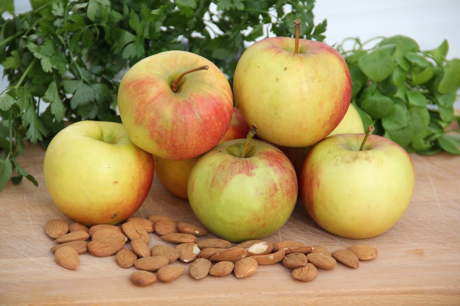 Äpfel und Mandeln auf einem Holzbrett
