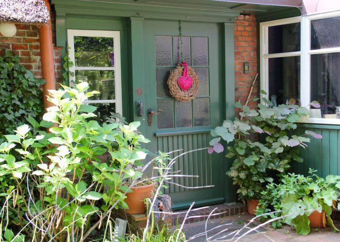 Haustür mit Blumenkübeln daneben