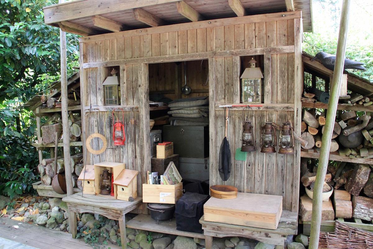 Holzhaus mit vielen Details wie Lampen, Vogelhäuschen, Holzvorräten