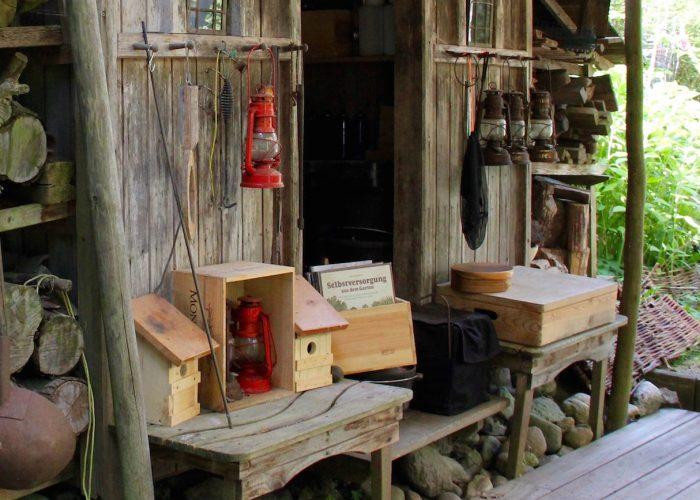 """Gaslampen, Vogelhäuschen, Holzvorräte und eine Bücherkiste mit John Seymours Buch """"Selbstversorgung aus dem Garten"""""""