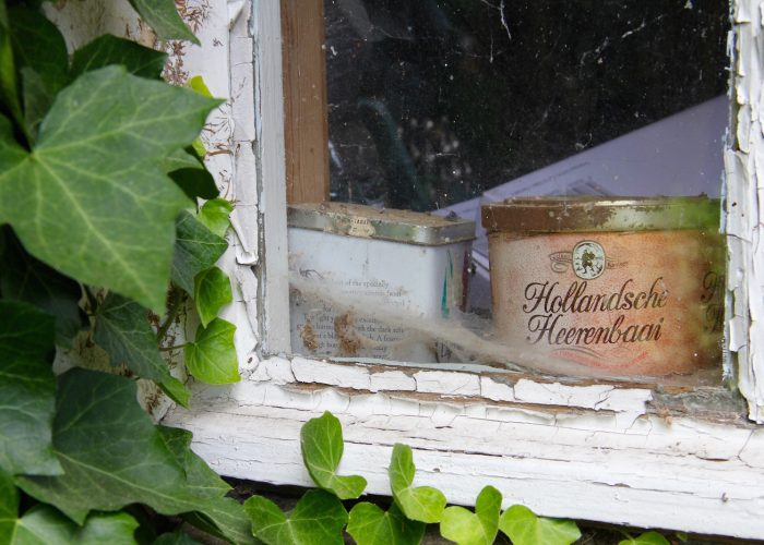 Alte Tabakdose hinter einer Fensterscheibe