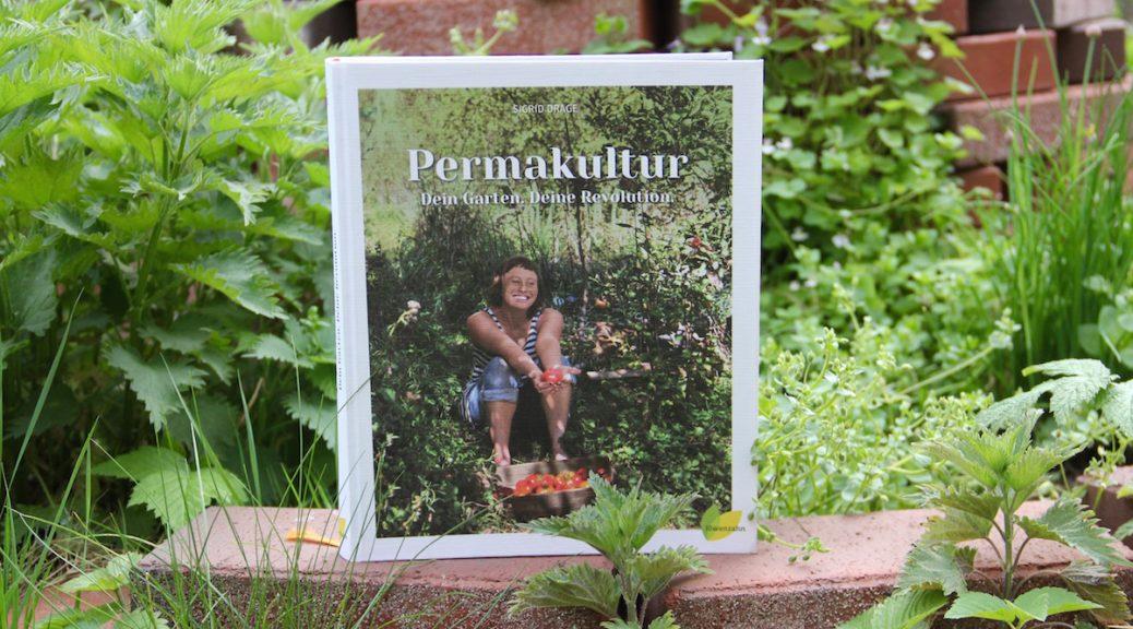 """Buch """"Permakultur"""" von Sigrid Drage auf dem Rand einer Kräuterspirale"""