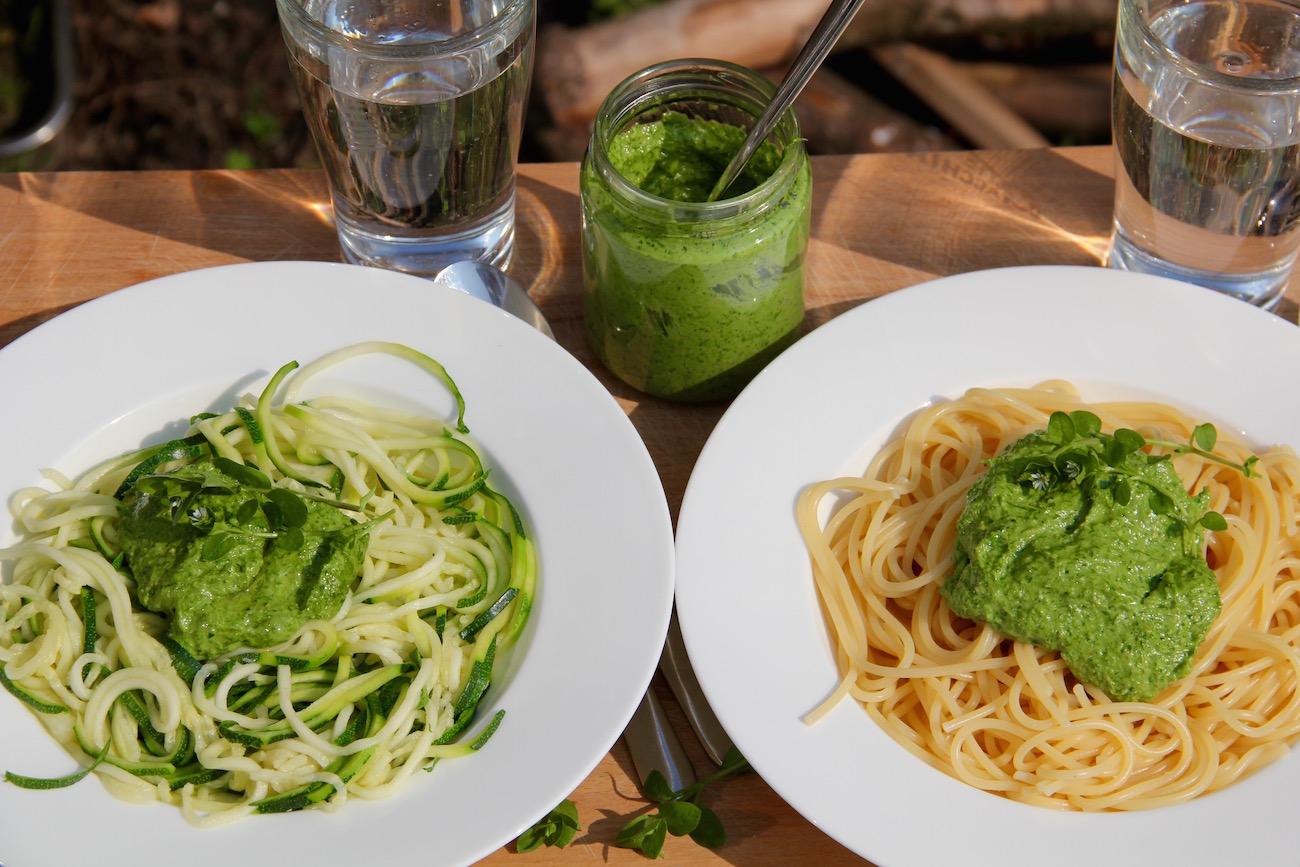 Pesto mit Zucchini-Nudeln angerichtet auf dem einen Teller und mit normalen Spaghetti auf dem anderen