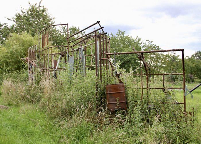 Rostende Gitter, Tonnen und andere Metallteile als Kunstobjekt am Waldgarten